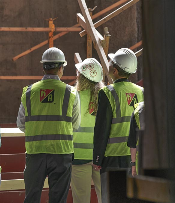 Three KA workers inspect a site