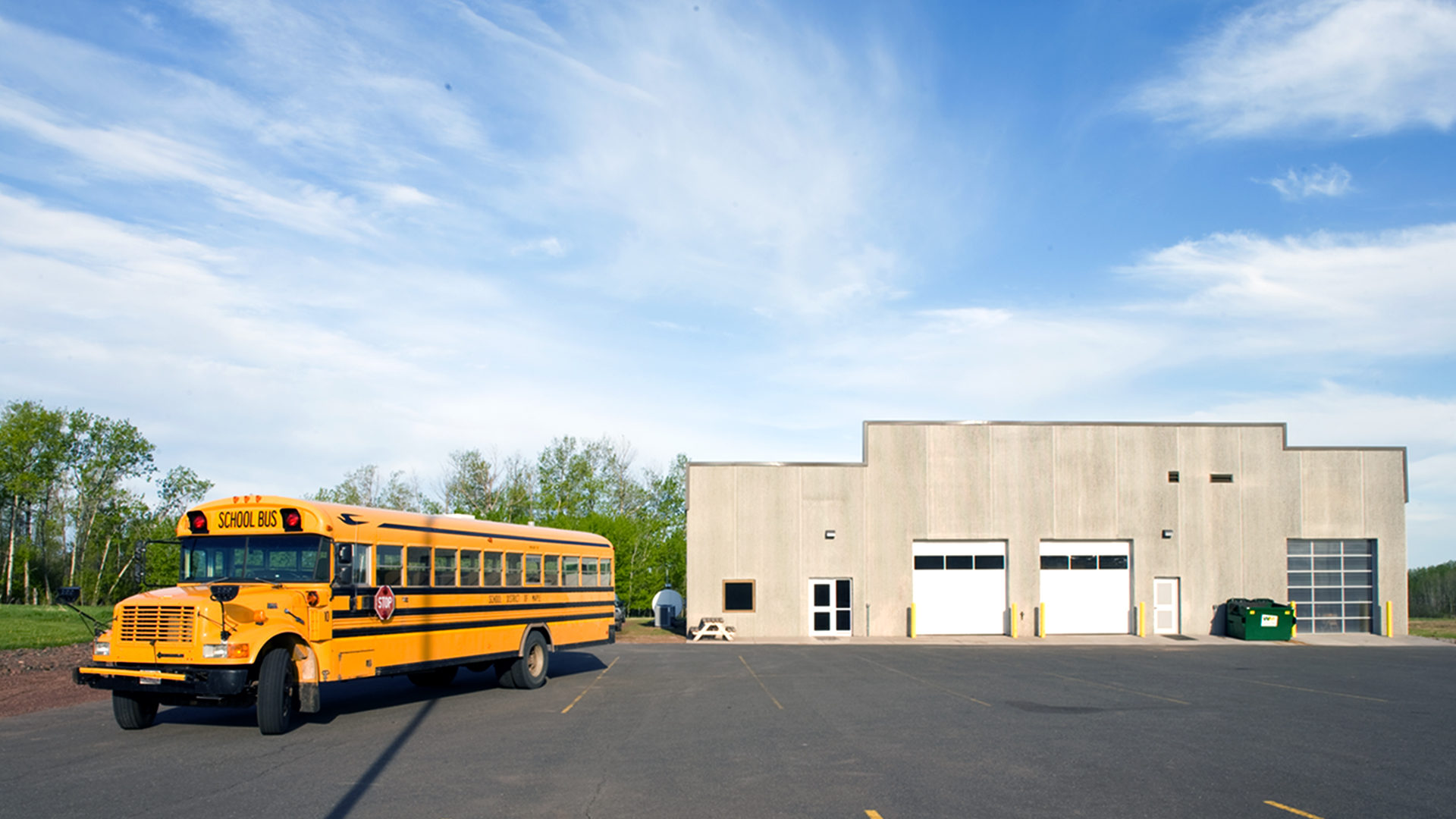 Maple School Transportation Building Poplar WI Exterior View with Bus Parked In Front