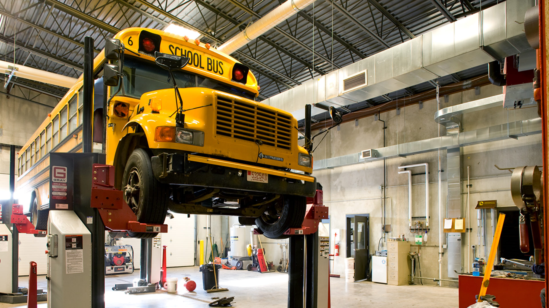 Maple School Transportation Building Poplar WI Interior Garge with a Bus on a Lift