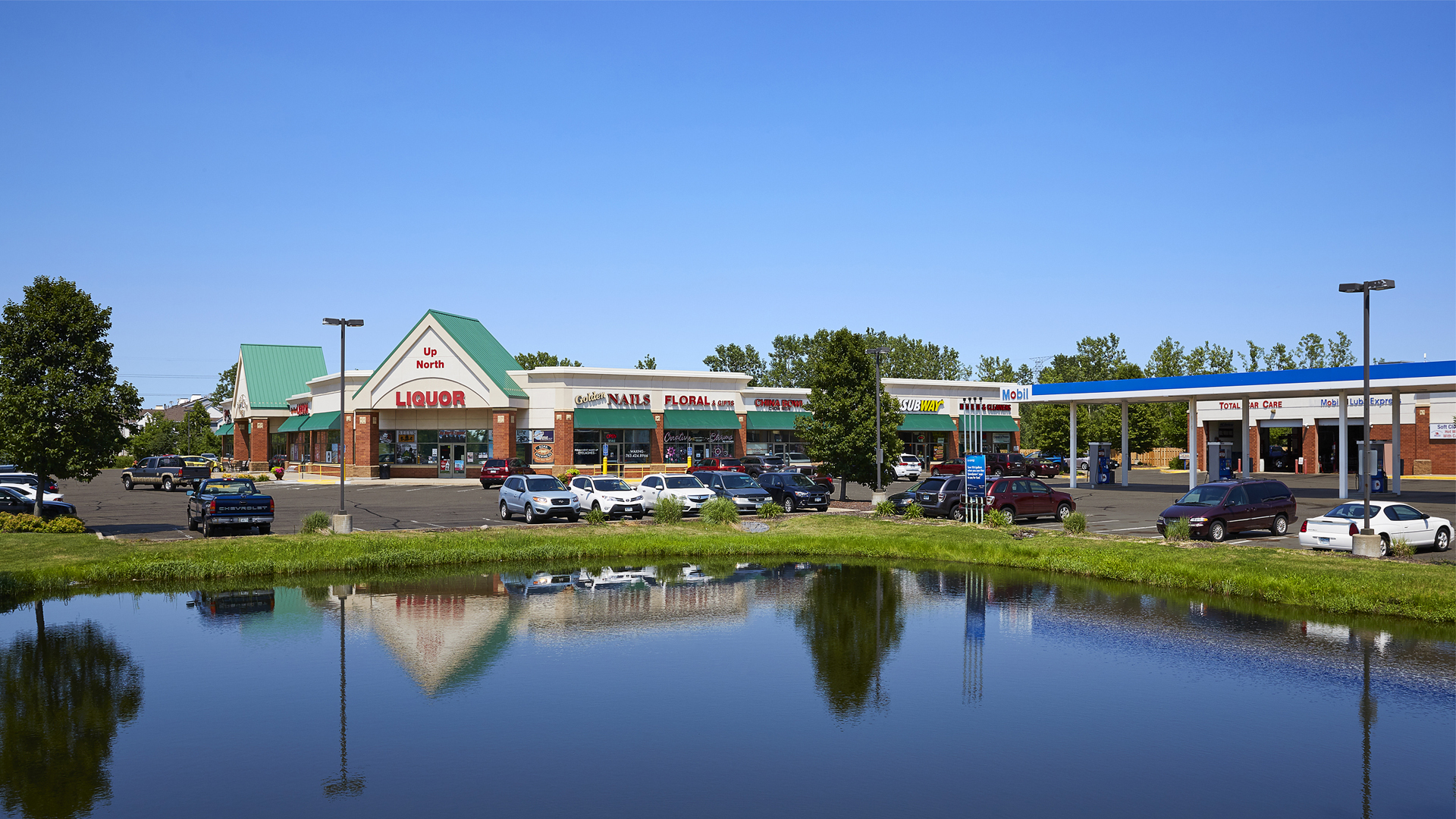 Pinebrook Centre Brooklyn Park MN retail strip mall full view shot from across pond