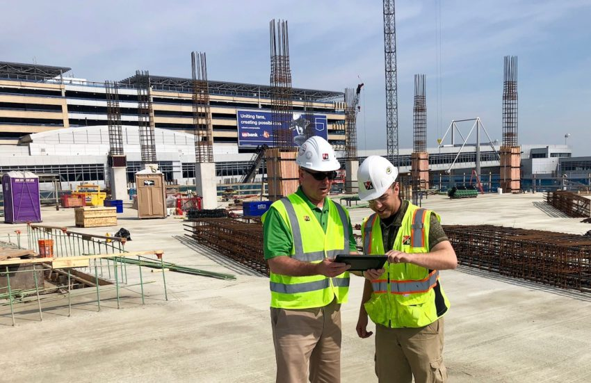 2 construction workers looking at an iPad