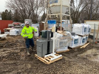 Construction worker at a hand washing station. Extra sanitizing measures are being taken on job sites to slow the spread of COVID-19.